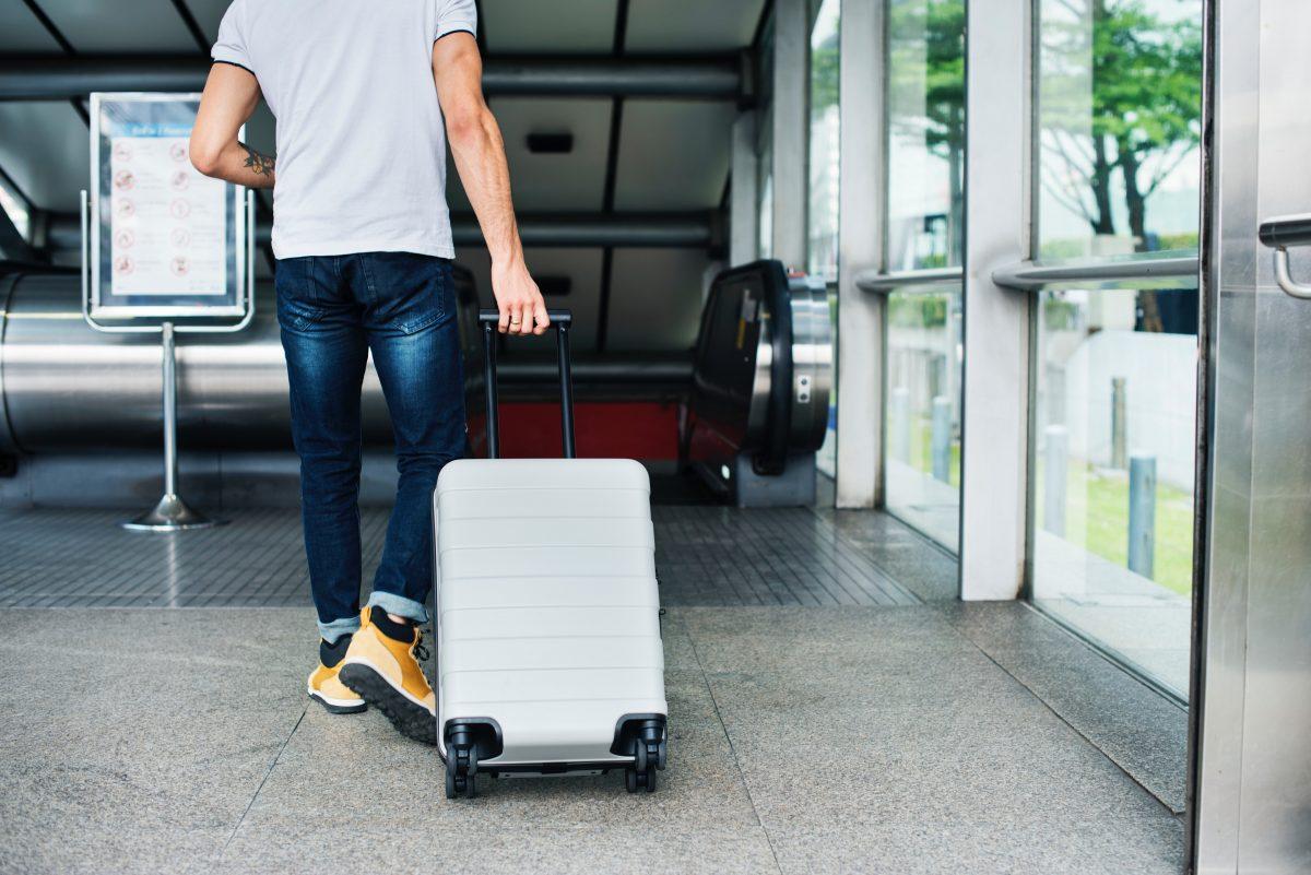 Jeune voyageur avec une valise dans un aeroport ou une gare