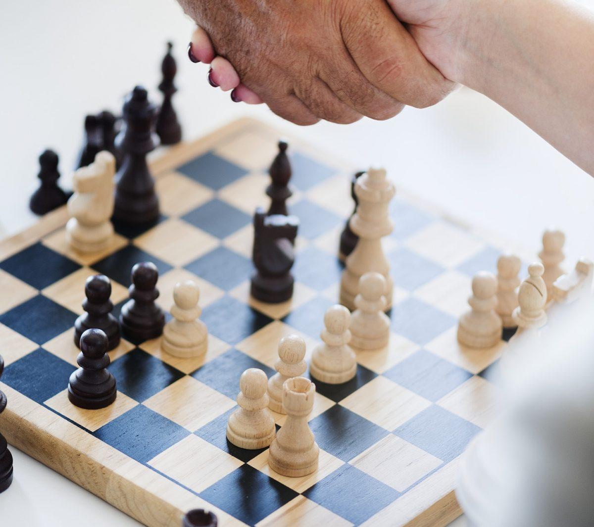 Poignée de main au dessus d'un jeu d'échec