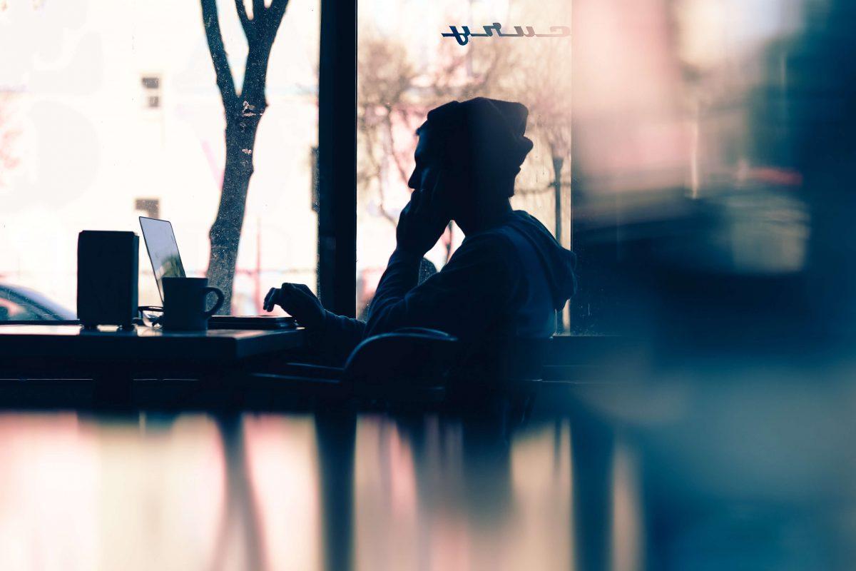 Homme dans un café qui discute au téléphone